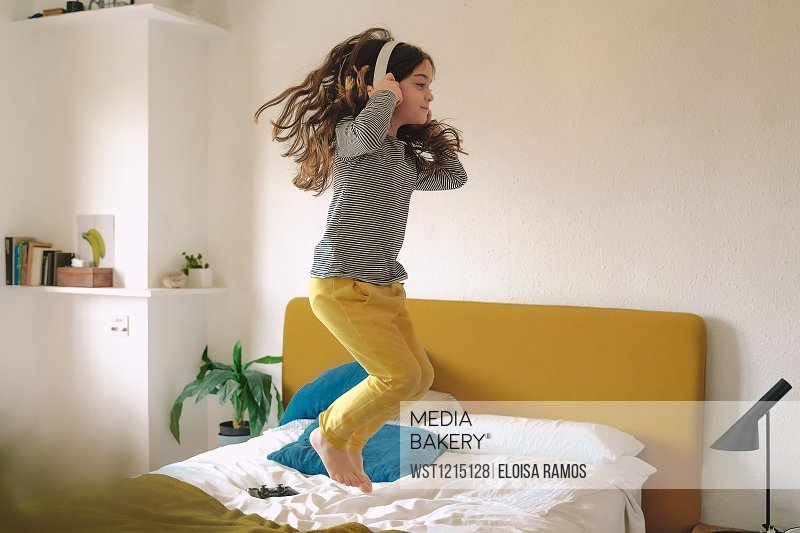 Girl jumping on bed and listening music with headphones