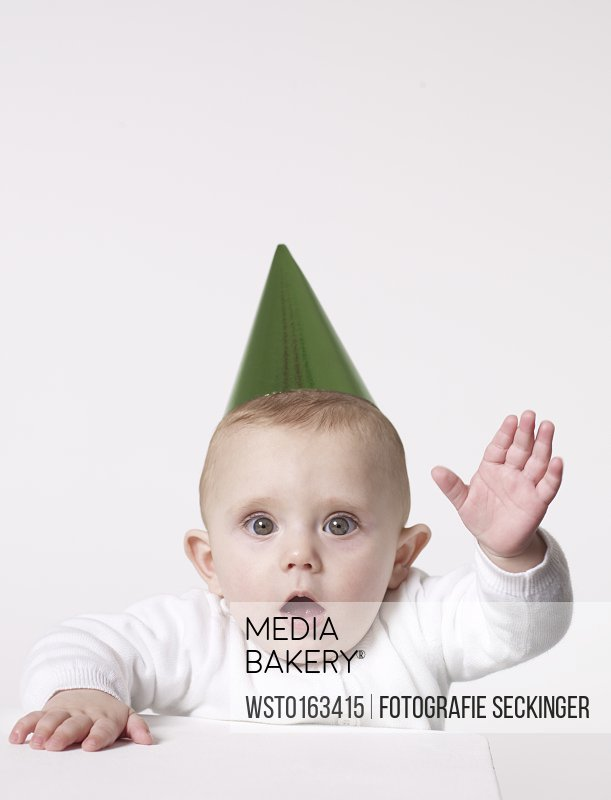 Amazed baby wearing party hat