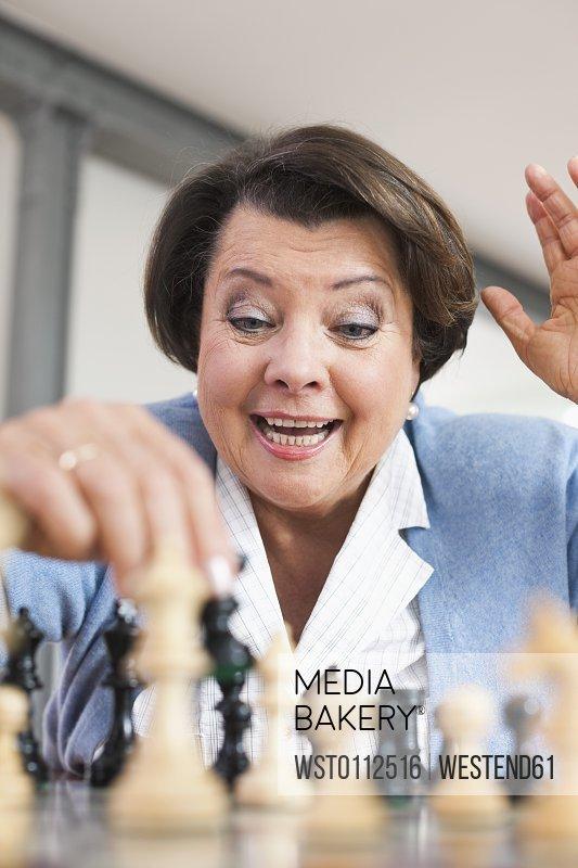 Senior woman playing chess game