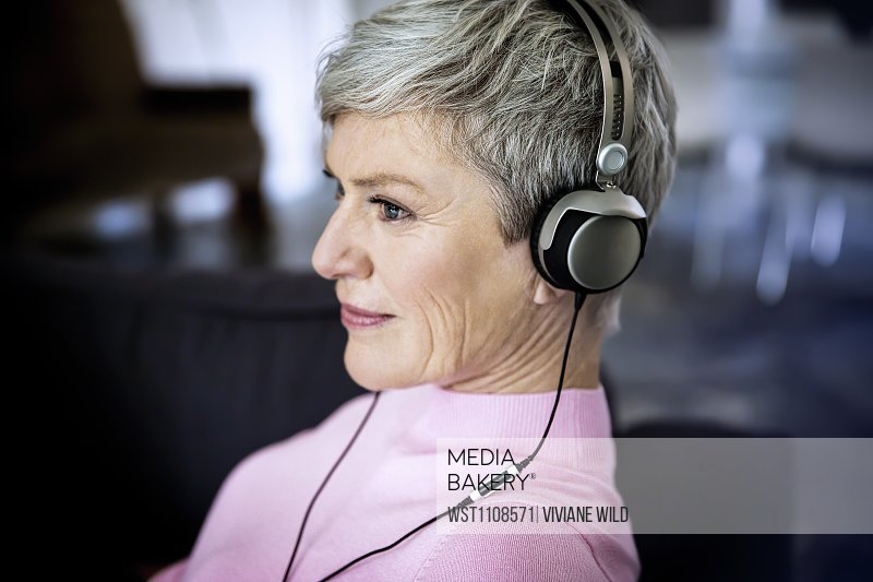 Content mature woman listening music with headphones at home