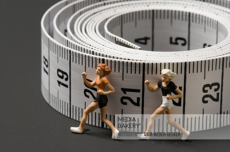 Female figurines with measuring tape on black background