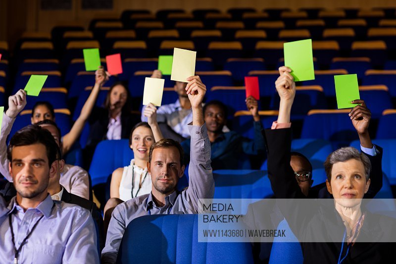 Business executives show their approval by raising hands at conference center