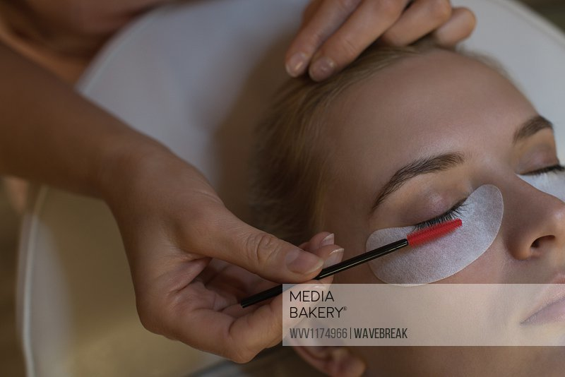 Beautician giving eyelash extension treatment to female customer in parlour