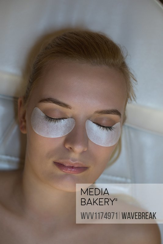 Close-up of woman getting eyelash extension treatment in parlour