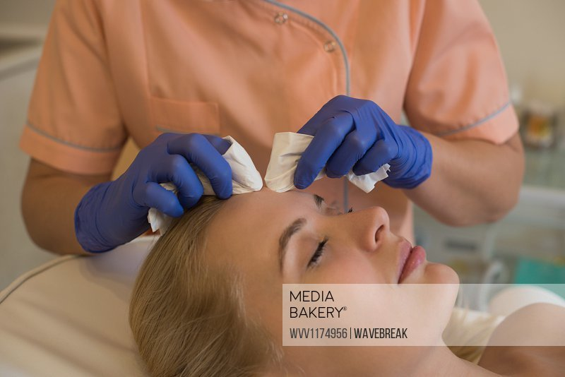 Beautician giving beauty treatment to female customer with a machine