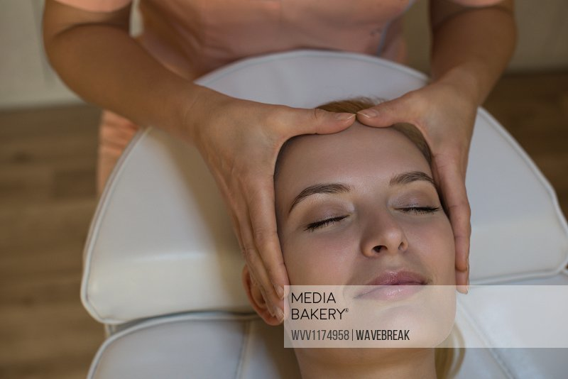 Beautician giving face massage to female customer at parlour