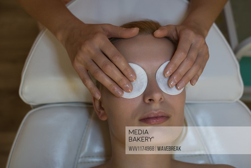 Beautician placing an beauty masks on female customer eyes in parlour
