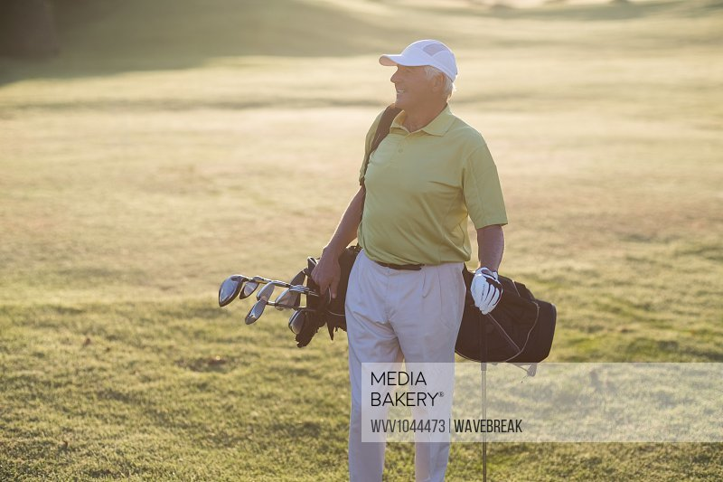 Happy man carrying golf bag while standing on field